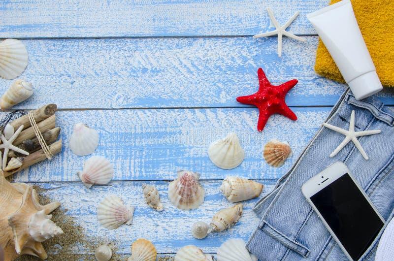 Concetto del mare della spiaggia di estate Fondo di legno blu con differenti accessori, coperture, stelle marine, asciugamano, pr fotografia stock libera da diritti