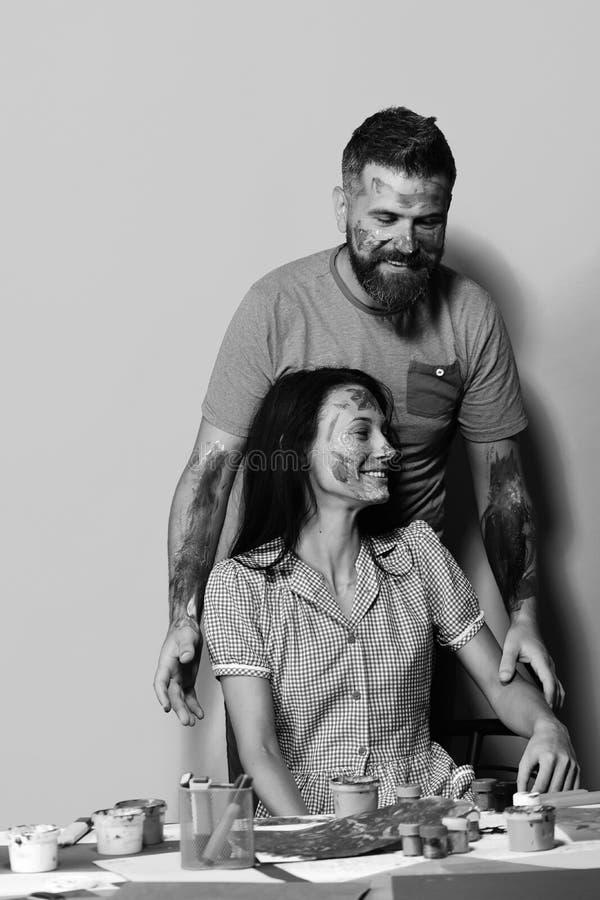 Concetto del mestiere e di body art Coppie nell'amore con i fronti dipinti con la gouache su fondo blu Famiglia degli artisti dal fotografia stock