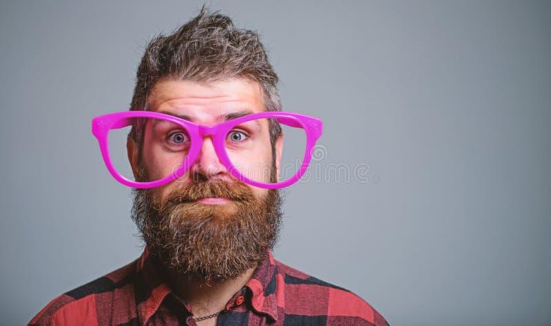 Concetto del nerd Pantaloni a vita bassa che guardano da parte a parte degli occhiali rosa giganti La barba dell'uomo ed il front fotografia stock libera da diritti