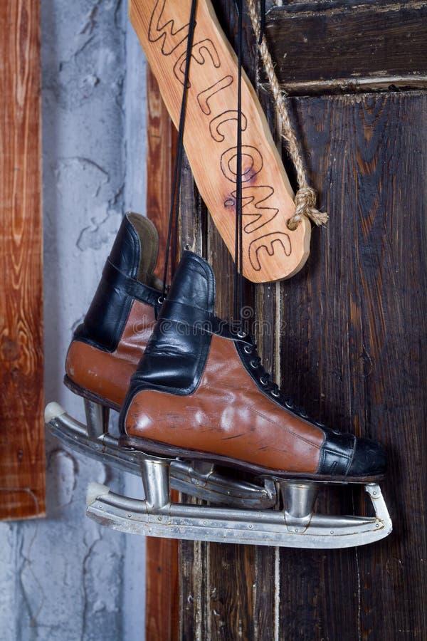 Concetto del nuovo anno dei pattini d'annata dell'hockey che appendono su una parete di legno accanto ad un benvenuto di detto de fotografie stock libere da diritti