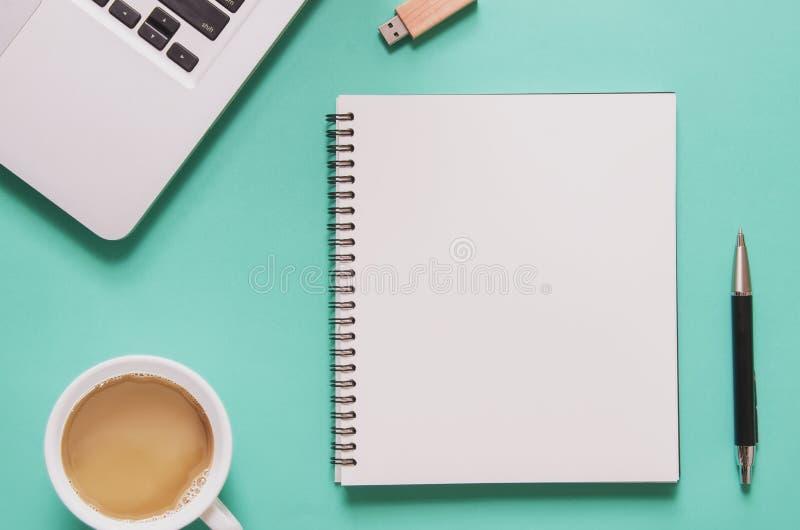 Concetto del posto di lavoro dell'ufficio Computer portatile del computer con il taccuino in bianco, tazza di caffè, penna, azion fotografie stock