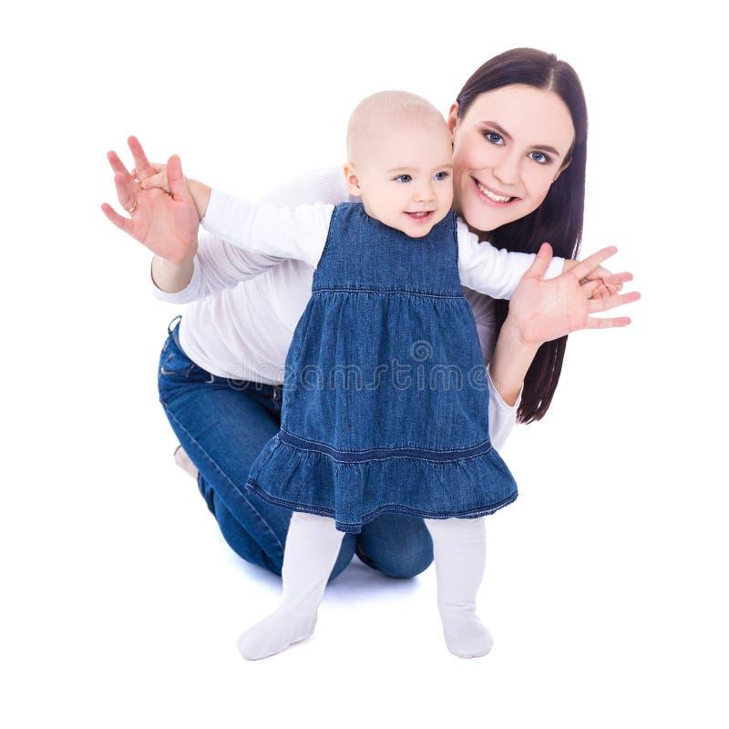 Concetto del primo punto - giovane madre con la neonata che impara a wal immagini stock libere da diritti