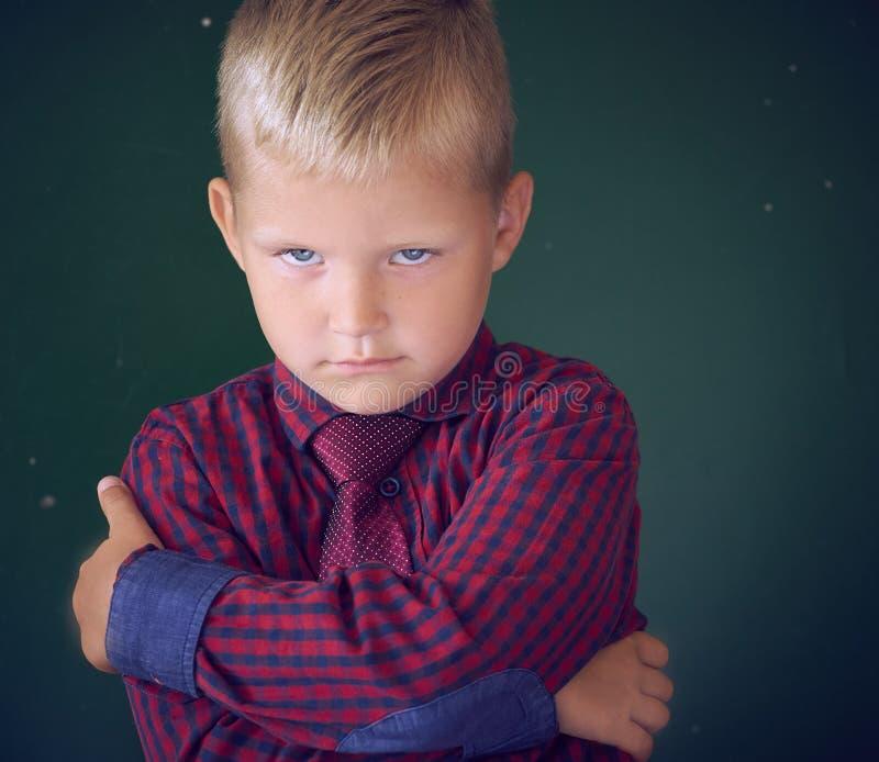 Concetto del ragazzo di scuola oppresso Piccolo il ragazzo caucasico triste ed arrabbiato sta abbracciandosi con le sue mani che  immagine stock libera da diritti