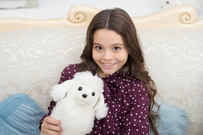 Concetto del regalo di Natale Giocattolo bianco della peluche del cane della piccola tenuta allegra sveglia della ragazza del bam immagini stock libere da diritti