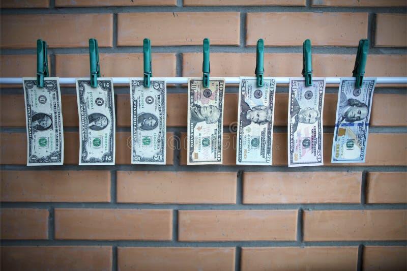 Concetto del riciclaggio di denaro - i dollari stanno asciugando sull'assicella sopra sul fondo del muro di mattoni immagini stock