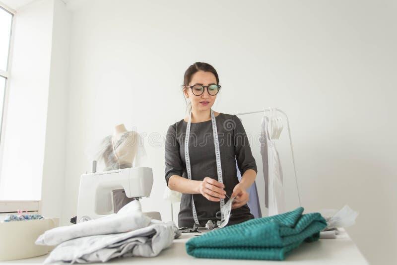 Concetto del sarto da donna, dello stilista, del sarto e della gente - ritratto di una cucitrice sul lavoro nel suo proprio studi fotografie stock libere da diritti