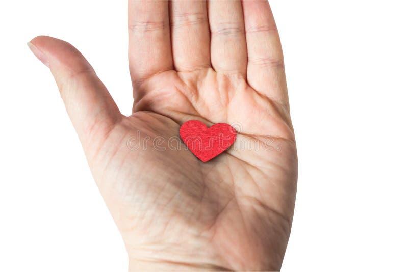 Concetto del segno rosso del cuore tenuto a disposizione su fondo bianco Vista superiore, percorso di ritaglio fotografie stock libere da diritti