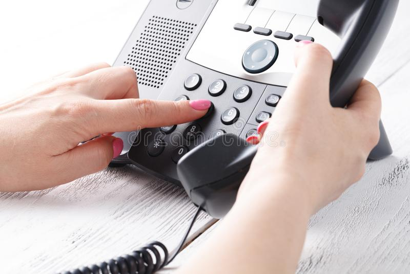 Concetto del telefono dell'ufficio o della call center, numero femminile della stampa del dito su phonepad fotografie stock libere da diritti