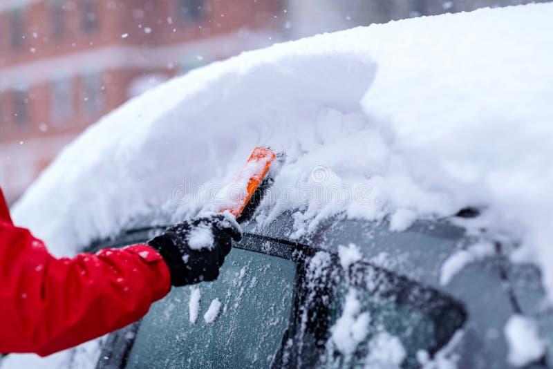 Concetto del trasporto, dell'inverno, del tempo, della gente e del veicolo - equipaggi la neve di pulizia dall'automobile con la  immagine stock libera da diritti