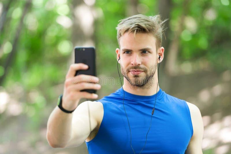 Concetto dell'aggeggio di sport Lista musicale radiofonica di messa a punto del telefono cellulare dell'atleta prima di runnig Sm immagini stock libere da diritti