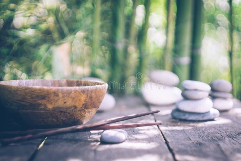 Concetto dell'alimento della disintossicazione: una ciotola di legno vuota, bastoncini di legno, bambù, pietre su una vecchia tav immagine stock