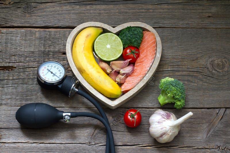 Concetto dell'alimento di dieta del cuore di salute con il calibro di pressione sanguigna immagini stock libere da diritti