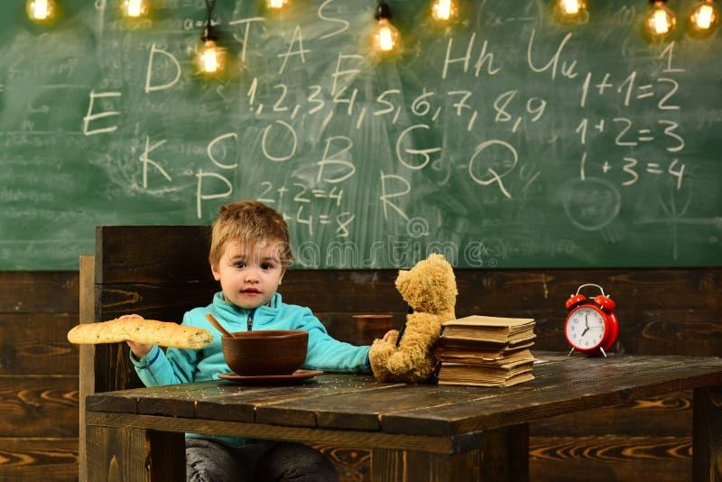 Concetto dell'alimento Il ragazzino mangia l'alimento alla scuola Il bambino gode dell'alimento saporito durante l'intervallo di  fotografia stock libera da diritti