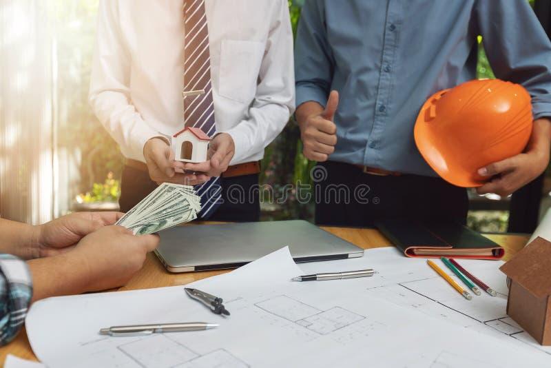 Concetto dell'architetto e dell'ingegnere, cliente che tiene soldi con il gruppo dell'ufficio dell'ingegnere, dell'agente immobil fotografia stock libera da diritti
