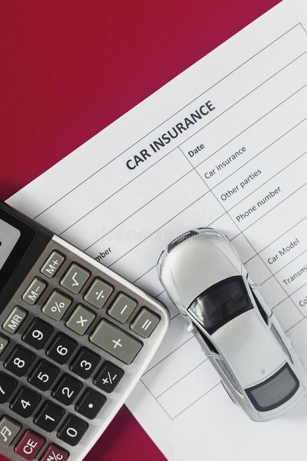 Concetto dell'assicurazione auto Assicurazione in bianco con l'automobile ed il calcolatore del giocattolo immagini stock