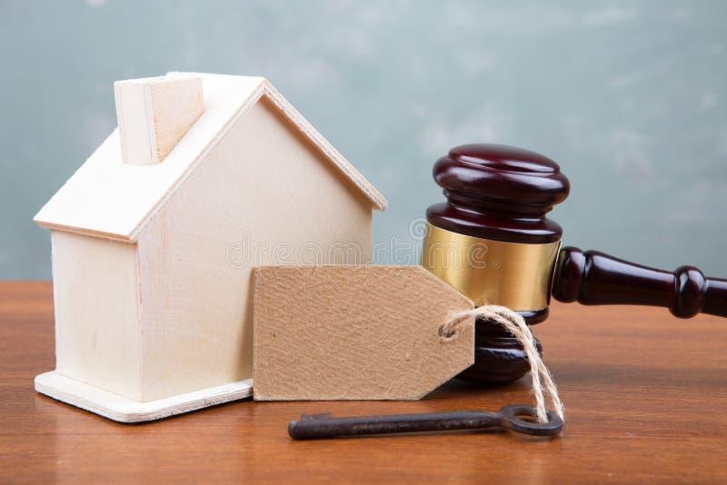 Concetto dell'asta di vendita del bene immobile - il martelletto e la casa modellano sulla tavola di legno immagine stock
