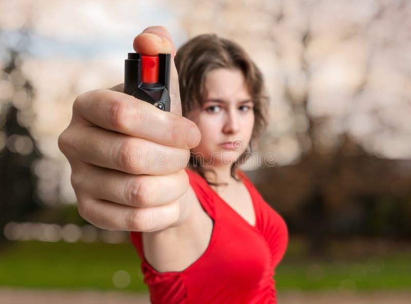 Concetto dell'autodifesa La giovane donna giudica lo spray al pepe disponibile immagine stock