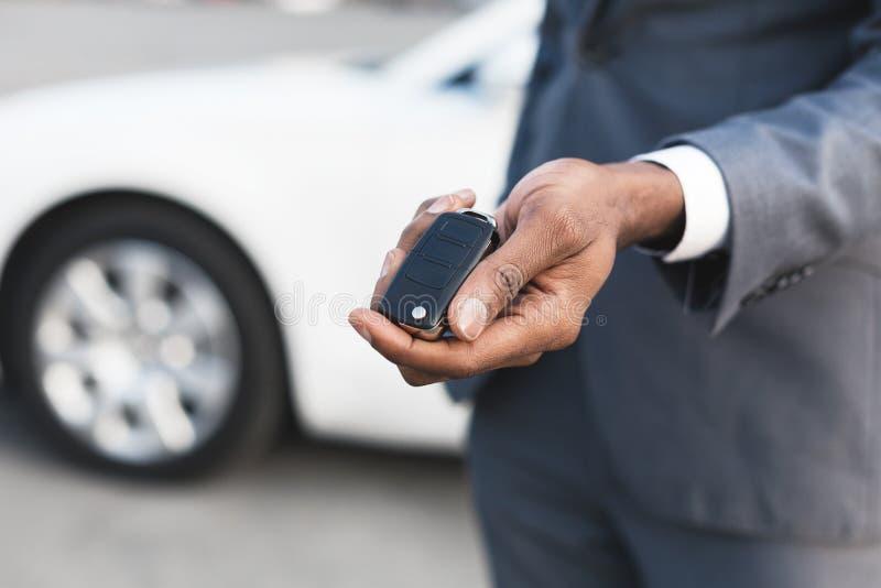 Concetto dell'autonoleggio Chiave di rappresentazione del giovane della sua nuova automobile fotografie stock libere da diritti