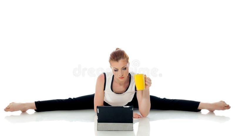 Concetto dell'elaborazione multitask - ginnasta che lavora al PC fotografia stock libera da diritti