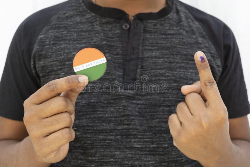 Concetto dell'elezione indiana, autoadesivo della tenuta della persona del voto per il migliore indiano su fondo isolato immagini stock