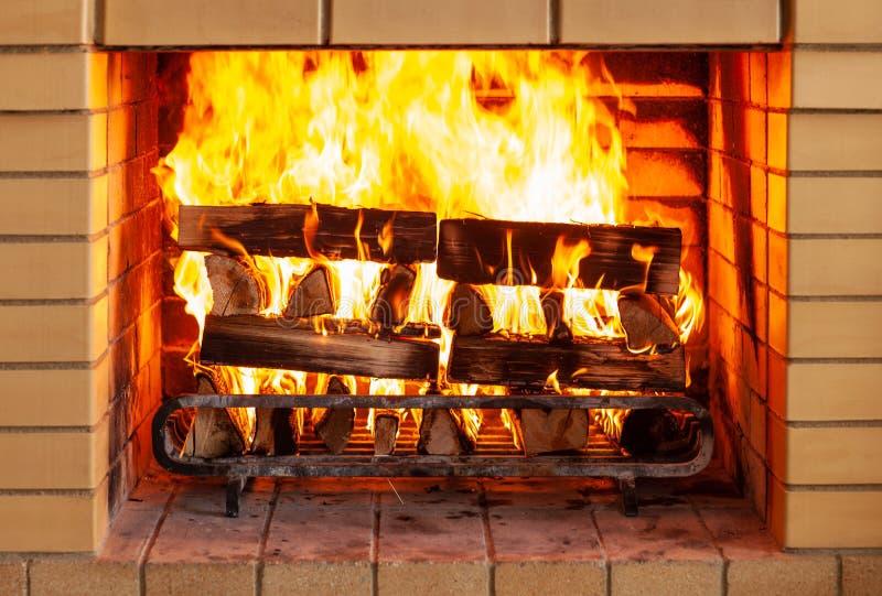 Concetto dell'incendio, di calore, del fuoco e di cosiness - vicino su del camino bruciante a casa immagine stock