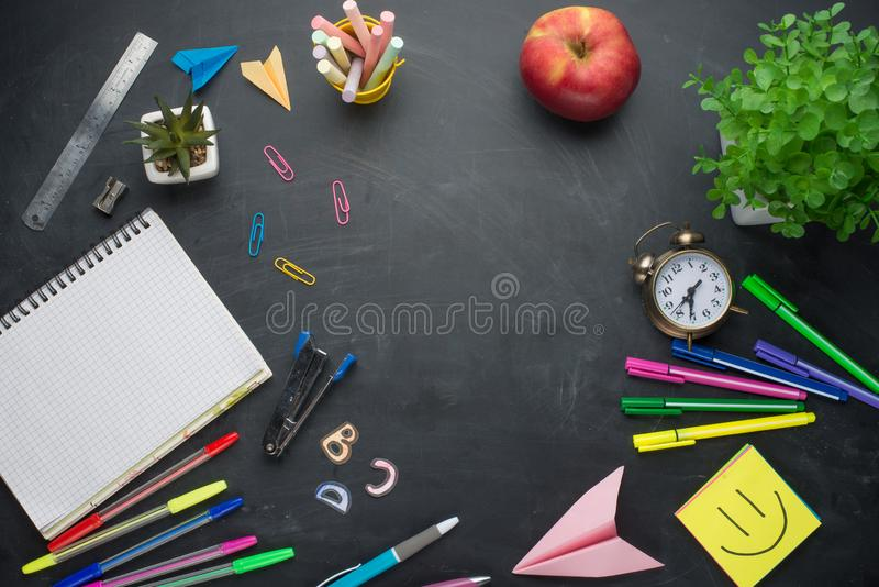 Concetto dell'insegna di nuovo alla sveglia della scuola, cancelleria del taccuino di Apple della matita sul fondo della lavagna  immagine stock