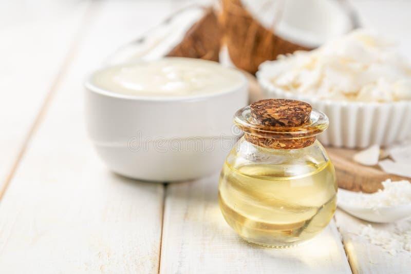 Concetto dell'olio di cocco di MCT - noci di cocco, burro ed olio su fondo di legno fotografia stock libera da diritti