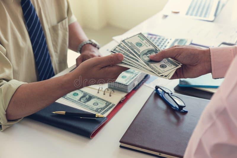 Concetto dell'ufficio che lavora, uomo d'affari di finanza e di affari che dà soldi al suo partner per il profitto dell'investime fotografia stock libera da diritti