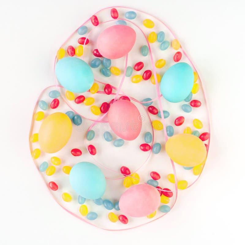 Concetto dell'uovo di Pasqua Uova variopinte e caramelle con il nastro rosa del raso su fondo bianco isolato Disposizione piana fotografia stock libera da diritti