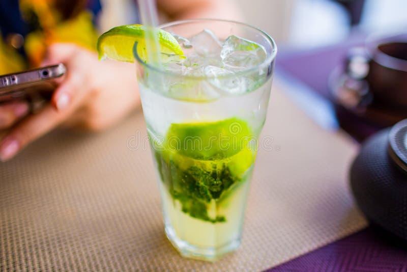 Concetto della bevanda alcolica Mojito con ghiaccio e calce nella fine di vetro su fotografia stock