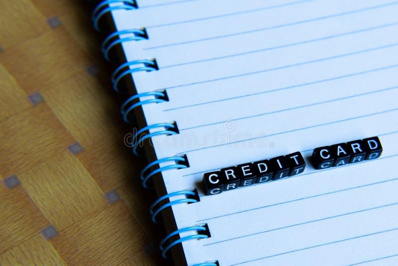 Concetto della carta di credito sui cubi di legno con i libri nel fondo fotografia stock
