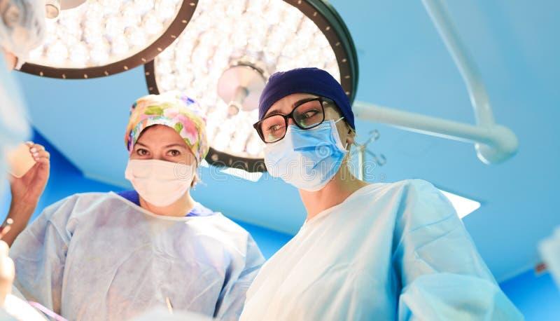 Concetto della chirurgia, della medicina e della gente - tre chirurghi nella sala operatoria all'ospedale durante il loro lavoro immagini stock libere da diritti