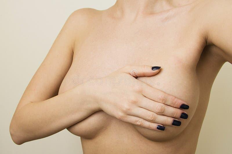 Concetto della chirurgia plastica Contols della donna il suo seno fotografie stock