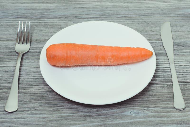 Concetto della dieta coperta di erica Carota saporita sul piatto bianco, forcella, knif fotografie stock libere da diritti