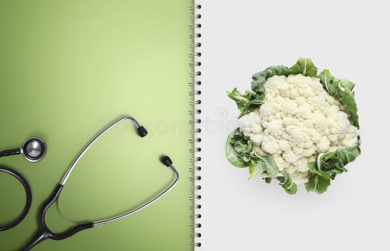 Concetto della dieta medica equilibrata con alimento sano, le pagine del taccuino della carta con lo stetoscopio ed il cavolfiore fotografie stock