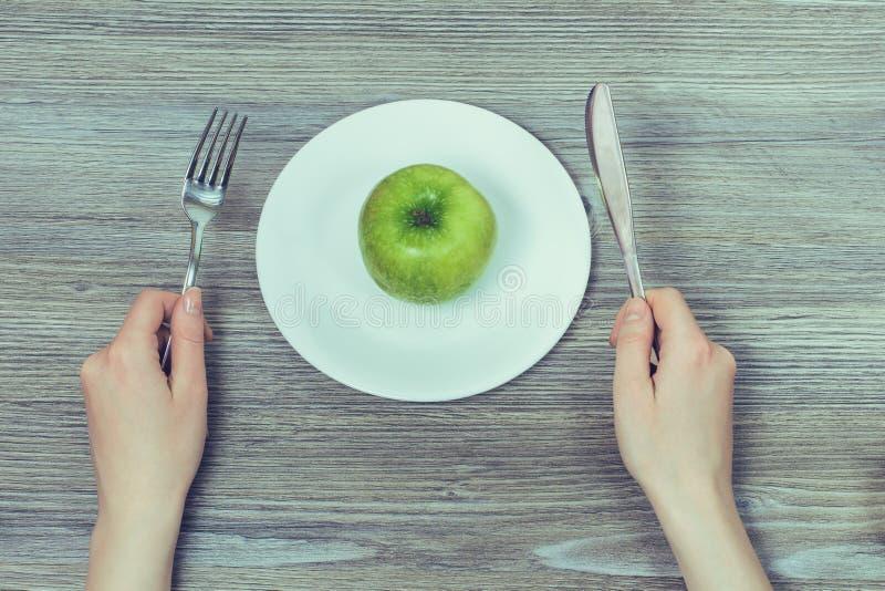 Concetto della dieta sana Mela saporita fresca verde sul piatto bianco fotografia stock libera da diritti