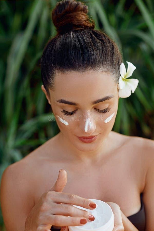 Concetto della donna di bellezza Cura di pelle Giovane modello con pelle molle che tiene crema cosmetica Trucco nudo Ritratto dei fotografie stock