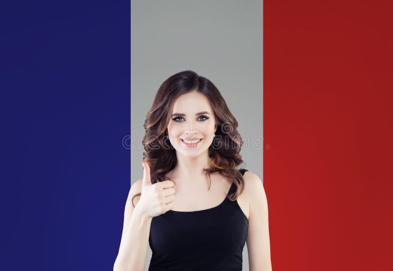 Concetto della Francia con il pollice felice di rappresentazione della donna su sul fondo francese della bandiera Viaggio in Fran fotografia stock