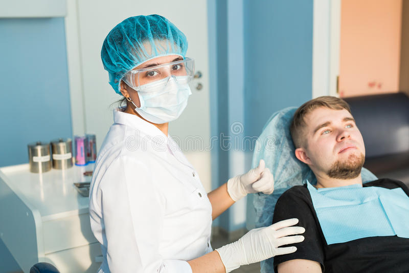 Concetto della gente, della medicina, di stomatologia e di sanità - giovane dentista femminile felice con gli strumenti sopra l'u immagine stock libera da diritti
