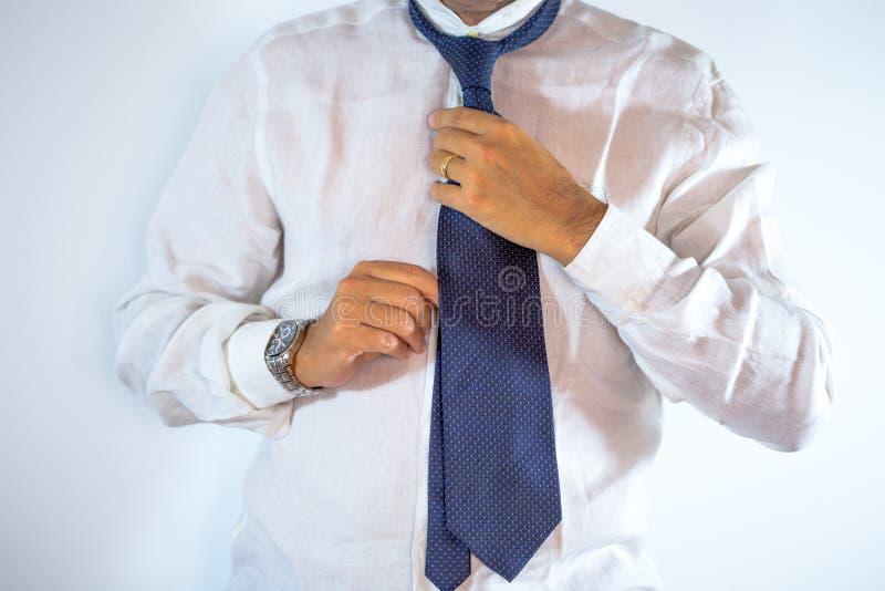 Concetto della gente, di affari, di modo e dell'abbigliamento - vicino su dell'uomo nell'agghindarsi della camicia immagini stock