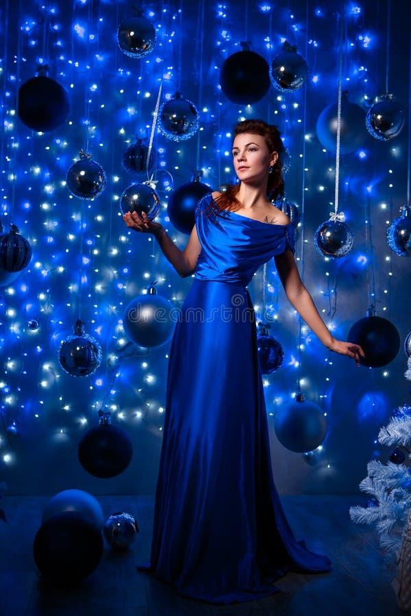 Concetto della gente, di stile, di feste, dell'acconciatura e di modo - giovane donna felice o ragazza teenager in vestito blu immagine stock libera da diritti