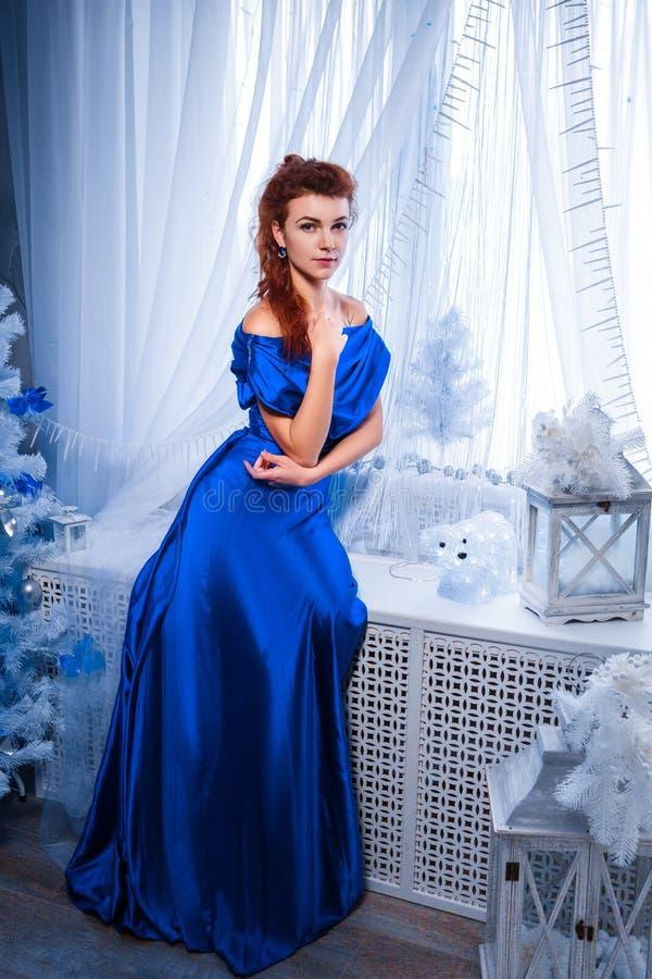 Concetto della gente, di stile, di feste, dell'acconciatura e di modo - giovane donna felice o ragazza teenager in vestito blu immagine stock