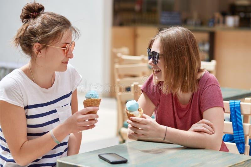 Concetto della gente, di stile di vita e di resto I pantaloni a vita bassa allegri hanno dente di riserva, mangiano il gelato del fotografie stock