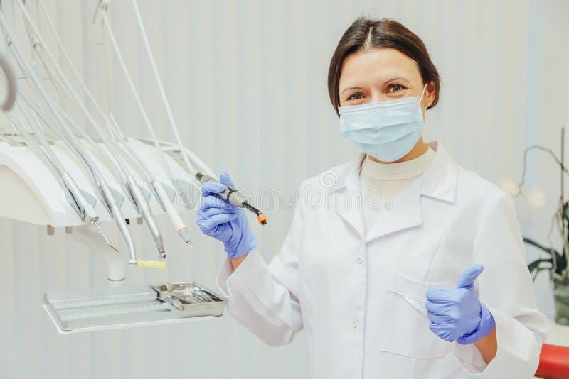 Concetto della gente, medicina, odontoiatria e sanità - dentista felice della giovane donna con gli strumenti sopra i precedenti  fotografia stock libera da diritti
