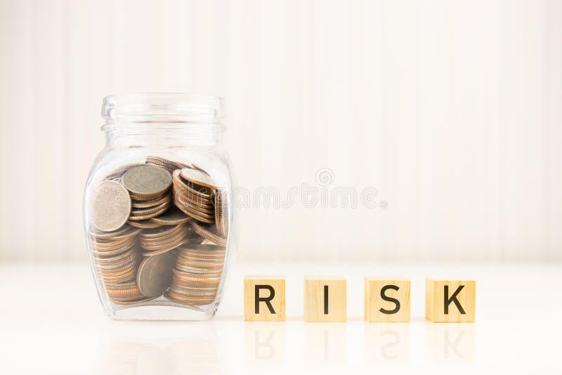 Concetto della gestione dei rischi Monete in barattolo con la parola RISCHIO del cubo del blocco di legno immagine stock libera da diritti