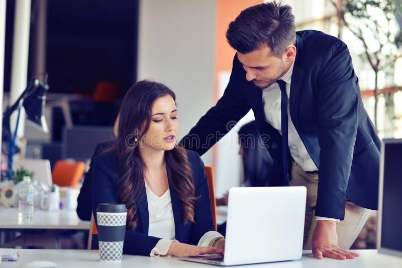 Concetto della giovane impresa con le giovani coppie multietniche in ufficio moderno che lavora al computer portatile fotografie stock libere da diritti