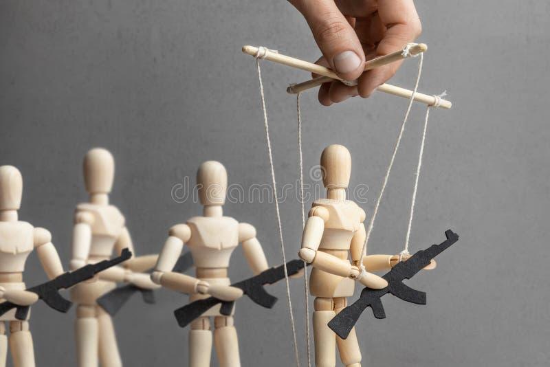 Concetto della guerra La gente con le armi, protesta munita, terroristi Il burattinaio controlla la bambola con la pistola, il pr fotografia stock