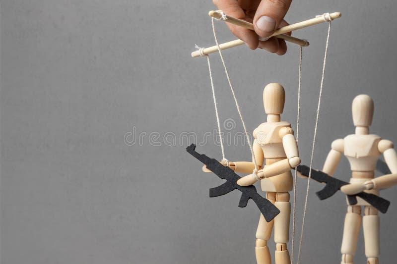 Concetto della guerra La gente con le armi, protesta munita, terroristi il burattinaio controlla la bambola con la pistola, il pr immagini stock libere da diritti