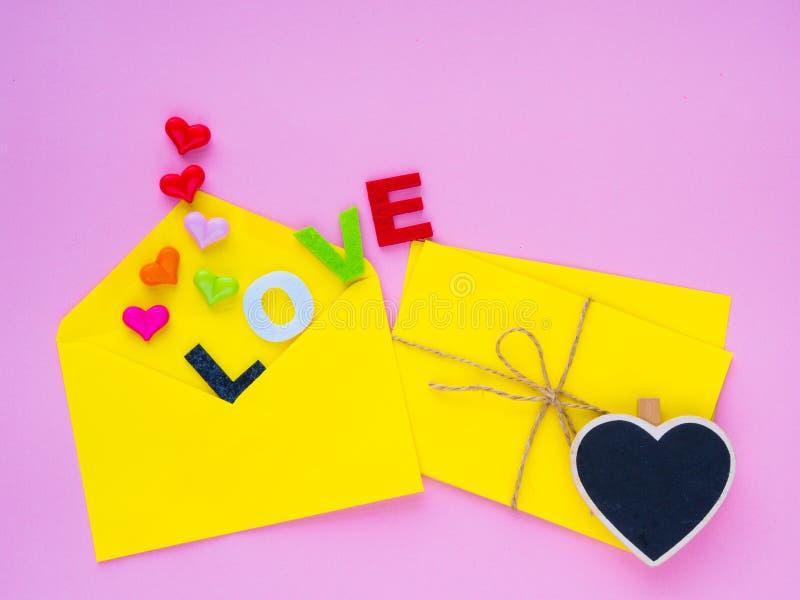 Concetto della lettera di amore La busta aperta e molte hanno ritenuto i cuori variopinto dei cuori con il testo di AMORE fotografie stock