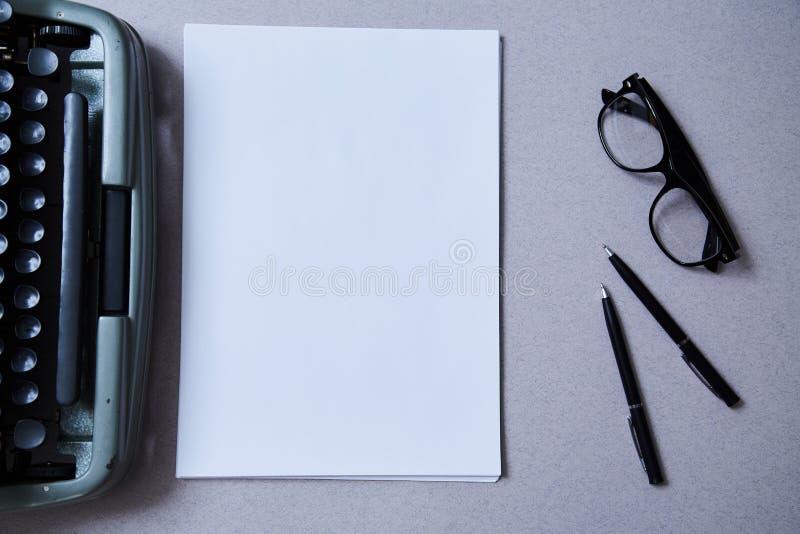 Concetto della letteratura, dell'autore e dello scrittore, di scrittura e di giornalismo: macchina da scrivere e vetri e un fogli immagine stock